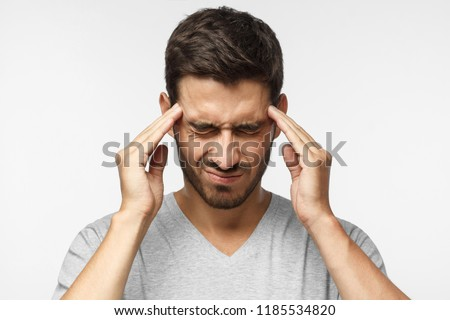 Portrait of young man isolated on gray background, suffering from severe headache, pressing fingers to temples, closing eyes #1185534820