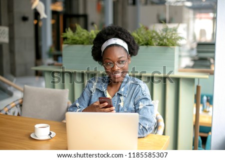 Young african customer client female in spectacles and jeans outfit beaming with joy, spending free time shopping online while sitting in cafe. #1185585307