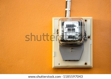 Electricity meter reading with copy space, Meter measuring instrument with sunset flare light, Watt-hour meter to measure electricity consumption use in home, Vintage orange background