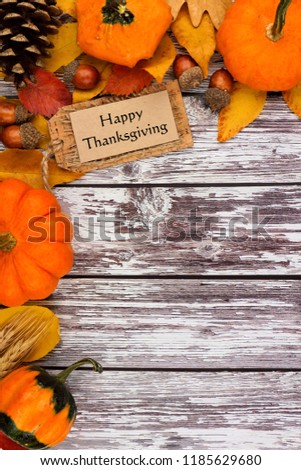 Happy Thanksgiving tag with autumn corner border of pumpkins and fall decor on an old white wood background. Copy space. #1185629680