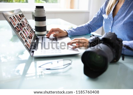 Editor Retouching Photos On Laptop With DSLR Camera On Desk