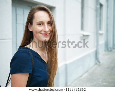 Hipster young redhead girl with freckles wearing blue dress and black backpack posing against city street building wall #1185781852