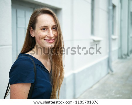 Hipster young redhead girl with freckles wearing blue dress and black backpack posing against city street building wall #1185781876