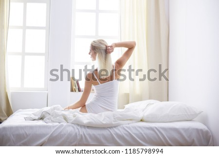 Woman stretching in bed after wake up, back view #1185798994