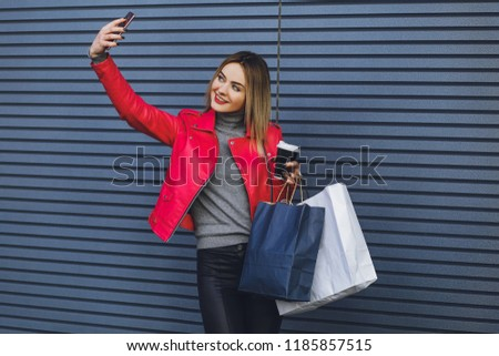 Beautiful young blonde girl doing selfie with shopping #1185857515