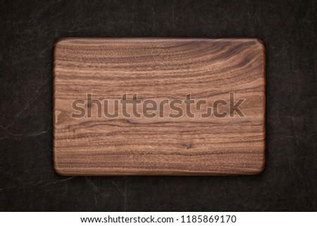 Handmade black walnut rectangular chopping board on handmade smeared burlap, walnut texture background #1185869170