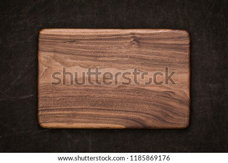 Handmade black walnut rectangular chopping board on handmade smeared burlap, walnut texture background #1185869176