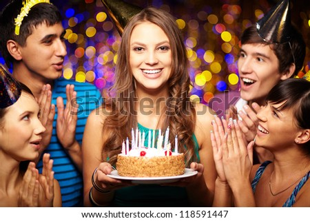 Portrait of joyful girl holding birthday cake surrounded by friends at party
