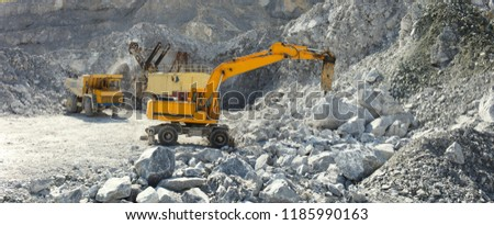 Hydraulic breaker hammer in a quarry for limestone mining with an excavator and a quarry truck in the background, panorama. #1185990163