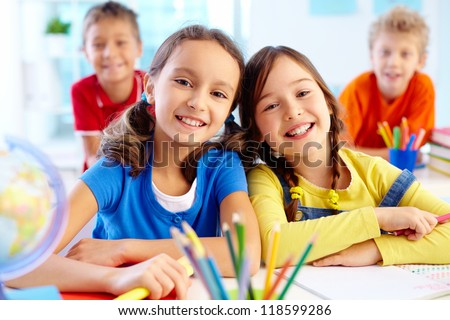 Portrait of two diligent girls looking at camera at workplace with schoolboys on background Royalty-Free Stock Photo #118599286