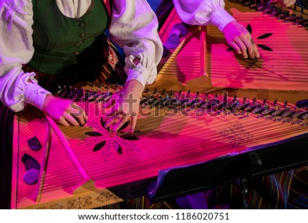 Hand playing on kokle a Latvian plucked string instrument belonging to the Baltic box zither family. #1186020751