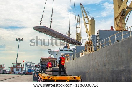 plate of steel slab being lifting by the ship crane, loading discharging operation for transfer the cargo shipment in export and import, works by stevedore labor in charge on jetty port terminal #1186030918