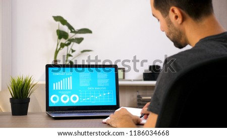 Business person working on his laptop looking at chart data in his living room #1186034668