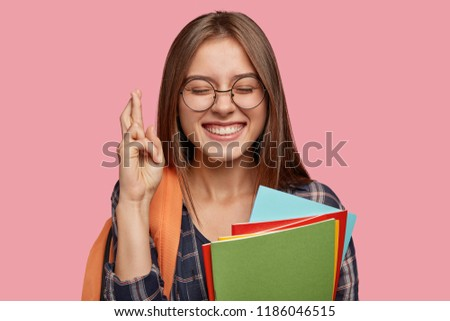 Intense cheerful schoolgirl with broad smile, crosses fingers for good luck, has satisfied expression, keeps eyes closed, carries rucksack, shows toothy smile, isolated over pink background. #1186046515