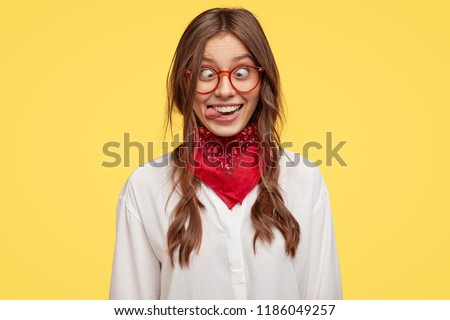 Photo of crazy girlfriend makes funny face, crosses eyes and sticks out tongue, plays fool, doesnt want to be responsible, being in good mood, models indoor against yellow studio background.