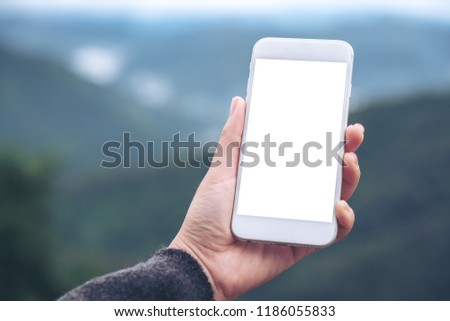 Mockup image of a hand holding and showing white smart phone with blank desktop screen in outdoor with blur green mountains background #1186055833