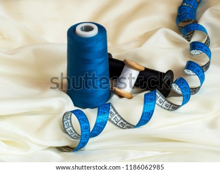 Three threads of different colors and blue twisted tape measure on beige cloth. Macro. Sewing concept #1186062985