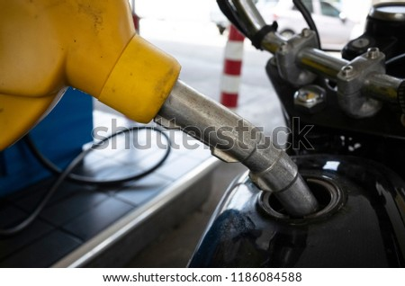 refueling motorbike at gas staion #1186084588