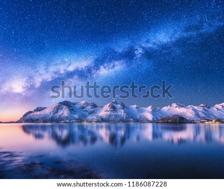 Bright Milky Way over snow covered mountains and sea at night in winter in Norway. Landscape with snowy rocks, starry sky, reflection in water, fjord. Lofoten Islands. Space. Beautiful milky way #1186087228