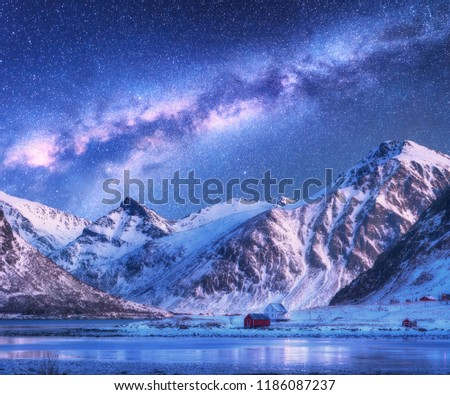 Milky Way above houses and snow covered mountains in winter at night. Starry sky, small village, snowy rocks in Lofoten Islands, Norway. Nordic landscape with milky way, water, ridge, buildings. Space #1186087237
