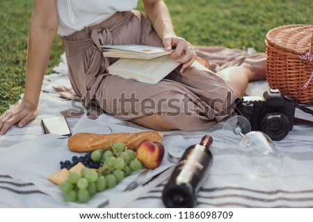 Cropped horizontal picture of girls legs having picnic on a grass in the Parc with blank bottle of wine and appetizers and a photo camera and reading a book. Blogger taking pictures of a picnic