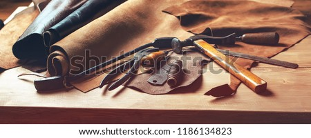 Shoemaker's work desk. Tools and leather at cobbler workplace. Set of leather craft tools on wooden background. Shoes maker tools on wooden table #1186134823