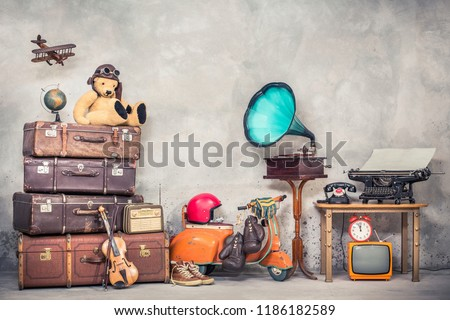 Retro Teddy Bear toy in aviator's hat, wooden plane, aged classic travel valises, globe, children pedal scooter, phonograph, typewriter, clock, TV, radio, old telephone. Vintage style filtered photo #1186182589