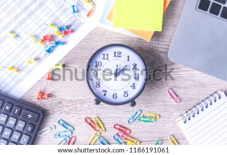 Time management concept. Composition with alarm clock on wooden table with laptop computer, stationary and calculator, top view above #1186191061