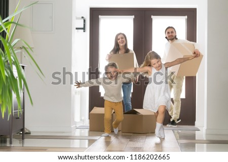 Happy married couple and little children arrive at new modern house. Husband and wife with cardboard boxes look at running inside excited daughter and son. Buy realestate, mortgage and moving concept #1186202665