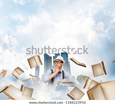 Young man writer in hat and eyeglasses using typing machine while sitting at the table among flying books with floating city and cloudy skyscape on background. #1186223956