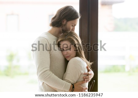 Sad young married couple embracing standing in living room opposite window at home. Sorrowful wife and husband feels unhappy, thinking about problems in relations, miscarriage, misbirth or infertility #1186235947