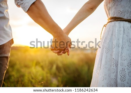 Couple hold hands in green field on sunset Royalty-Free Stock Photo #1186242634
