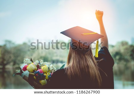 Back of view Graduate put her hands up and celebrating with certificate in her hand and feeling so proud and happiness in Commencement day,Education Success Concept #1186267900