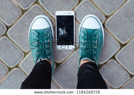 Smartphone with a broken display lies at the feet of a person on the asphalt