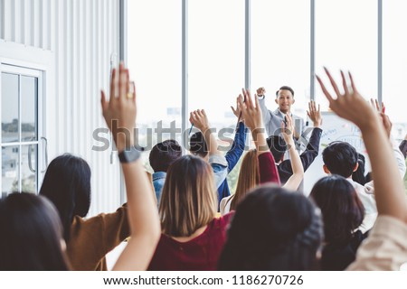 Group of business people raise hands up to agree with speaker in the meeting room seminar Royalty-Free Stock Photo #1186270726