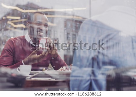 Keep smiling. Delighted brunette sitting opposite his girlfriend while doing proposal #1186288612