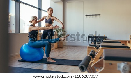 Fitness woman doing pilates workout sitting on an exercise ball at gym. Fitness trainer guiding a woman in pilates training. #1186289059