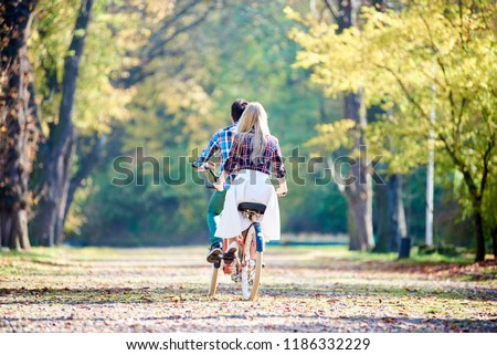 Back view of young tourist couple, man and blond long-haired woman cycling together tandem double bike by park or forest sunny alley covered with golden leaves on thick misty foliage background. #1186332229