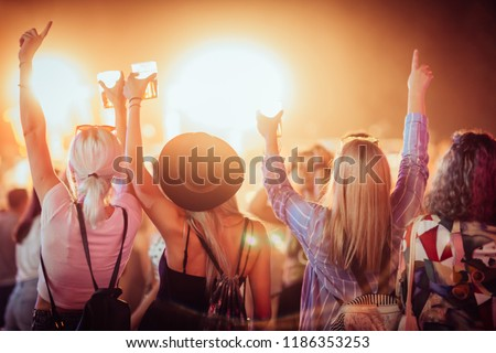 Back view of group of female friends at music festival drinking beer and dancing #1186353253