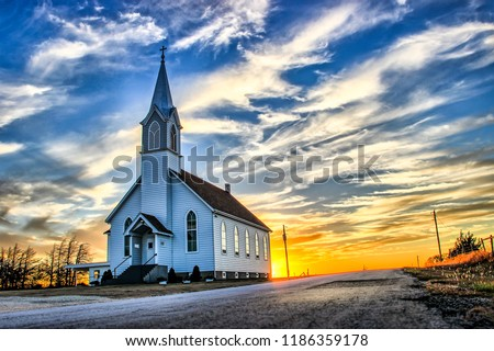 A Lone Wooden Church at Dusk with Sunset Clouds in Kansas American Midwest Prairie #1186359178