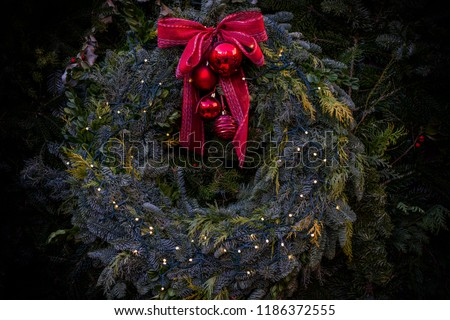 Green Christmas wreath from fir, pine and spruce with red ribbon bow and balls with decorations. Composed of fresh fir branches and ornaments in red. Christmas and New Year holiday background. #1186372555