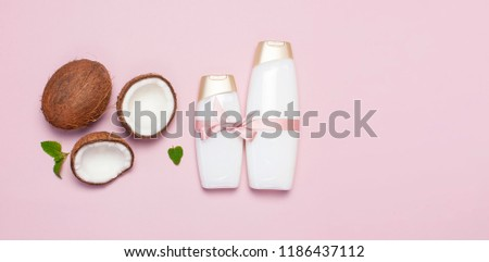 Organic cosmetics with shower gel, ripe coconut on pink colored background top view minimal flat lay style. Coconut oil, milk. Healthy skincare. Homemade cosmetic for peeling and spa concept.  #1186437112