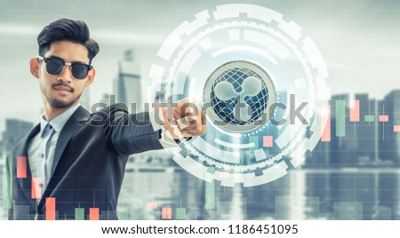 Ripple and cryptocurrency investing concept - Businessman pointing at Ripple (XRP) with modern business building and cityscape in the background. Blockchain technology. #1186451095