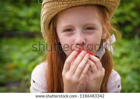 Red-haired girl eats ripe, juicy strawberries, sitting near a green garden with strawberries, lit by sunlight. #1186483342
