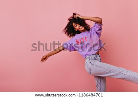 Beautiful shapely woman dancing with inspired face expression. Debonair black girl in purple shirt smiling on rosy background. #1186484701