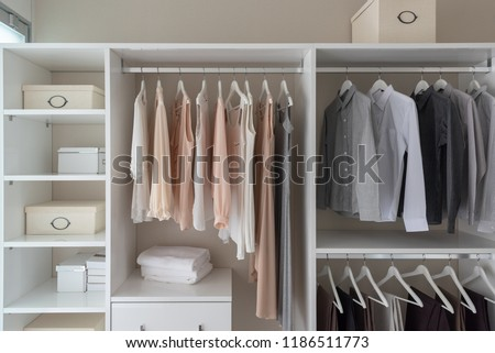 modern closet with clothes hanging on rail, white wooden wardrobe, interior design concept #1186511773