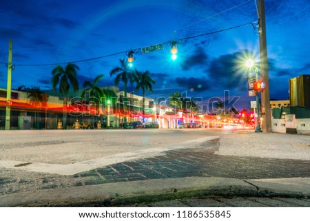 Night time long exposure of busy intersection in downtown Delray Beach Florida. Light trail from car vehicle traffic tail lights pass through green light and crosswalk countdown signal #1186535845