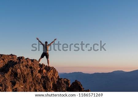 Man Stands on Rocks at Sunset on Death Valley mountain peak #1186571269