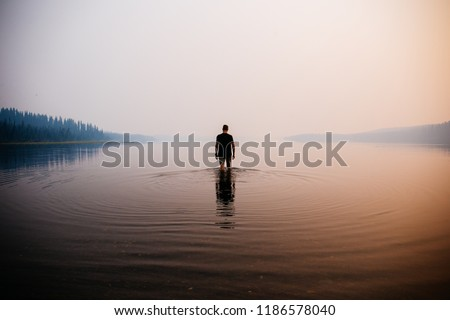 Man in the water knee deep. Smokey atmosphere. Spooky. Reflection in the water. Mountains and trees in the background. Royalty-Free Stock Photo #1186578040