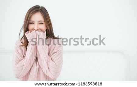 Portrait of young beautiful asian woman relax in bedroom. Smile happy asian girl hands cover face wear winter cloth. Beauty treatment perfect clear skin japanese woman makeup winter concept banner #1186598818